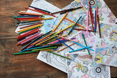 coloring pages with bright pencils on wooden table, top view