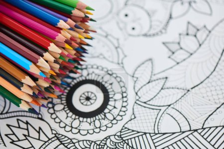 pile of bright rainbow crayons on coloring page, close-up