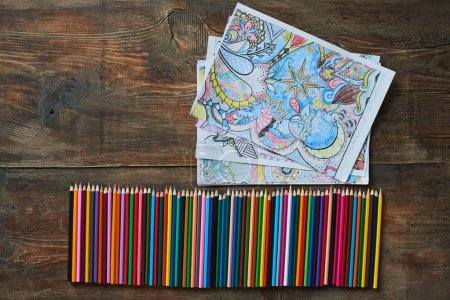 row of pencils with collection of coloring pages on table, close-up