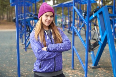 Photo for Woman athlete in sportswear standing with crossed arms on outdoor playground with equipment in woods - Royalty Free Image