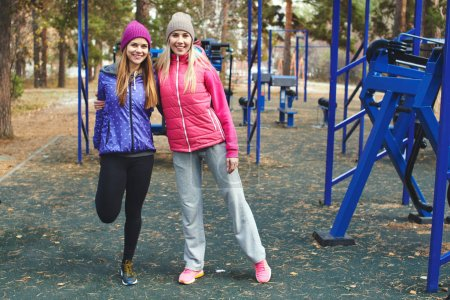 funny sporty friends hugging while standing on playground in forest