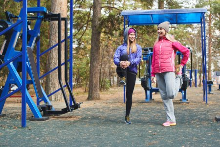 Photo for Two women stretching on outdoor playground in park - Royalty Free Image