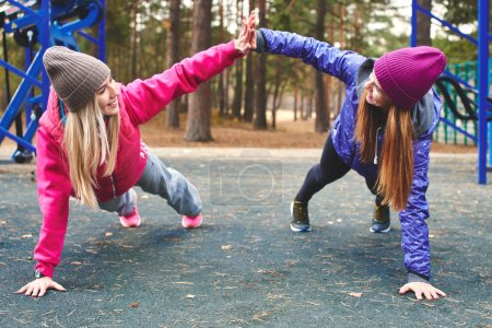 Photo for Two women in sportswear doing physical exercises on outdoor playground in woods,  healthy lifestyle concept - Royalty Free Image