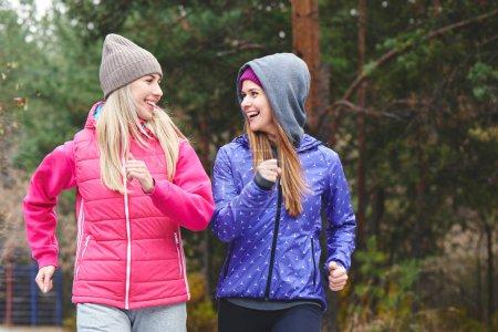 Photo for Beautiful women in warm sportswear running in autumn park - Royalty Free Image