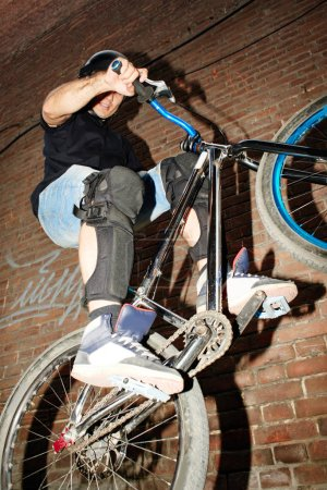 Photo pour Sport cycliste des sauts sur la roue arrière du cycle avec effort sur fond de mur de brique rouge floue - image libre de droit