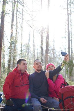 Photo pour Groupe de touristes prenant selfies dans les bois à la journée ensoleillée - image libre de droit