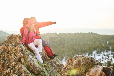 Photo for Man pointing forward while sitting with woman on top of mountain - Royalty Free Image