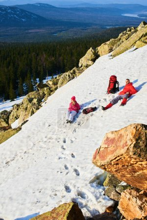 Photo for Tourist couple in love relaxing while lying on snowy slope in mountains at sunny day - Royalty Free Image