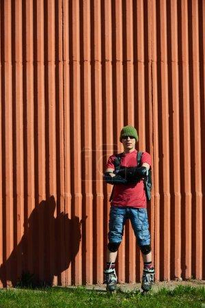 Photo pour Homme confiant avec les bras croisés en patins à roulettes debout près du mur rouge - image libre de droit