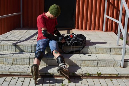 man in roller skates with abrasions on his knee sitting on stairs and searching in backpack tools for first aid