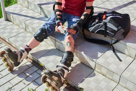man in roller skates sitting on stairs and wiping wound on knee, concept of first medical aid