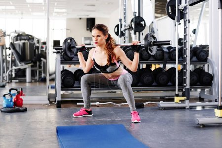 Fitness woman making squat with barbell in gym
