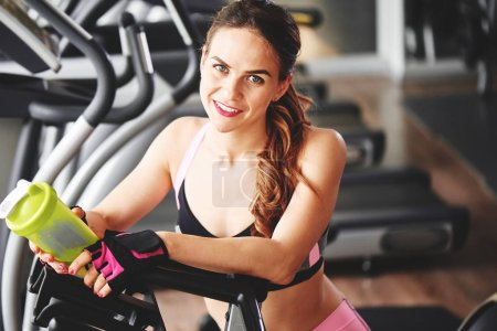 athletic woman holding sports bottle and looking at camera while leaning on exercise bike in gym