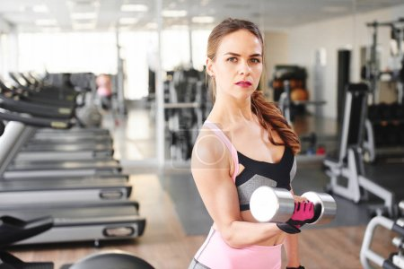 attractive fitness woman lifting dumbbell in gym