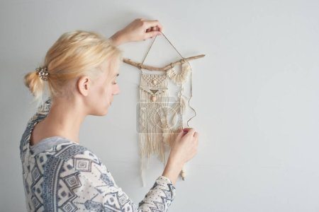 woman making canvas of threads, macrame decoration concept