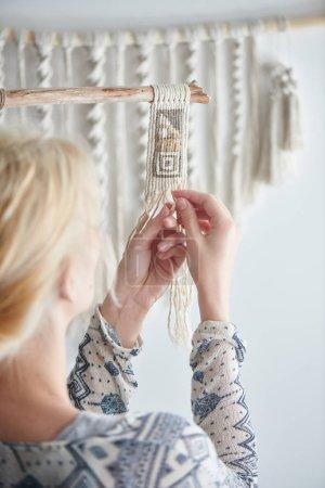 blonde woman weaving element of macrame decoration, female hobby concept