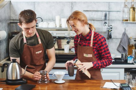 Photo for Male and female professional baristas in aprons working in coffee shop - Royalty Free Image