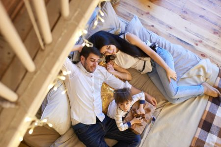 asian couple with son lying on bed in apartment, top view