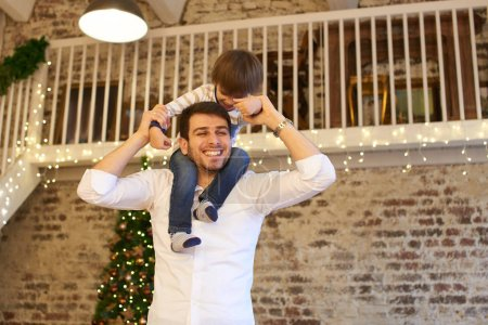 smiling father holding son on shoulders in apartment decorated for Christmas