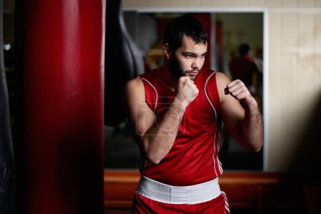 Portrait of aggressive fighter in boxing pose in gym with punching bag on background