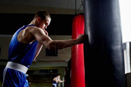 strong sportsman training with punching bag in gym