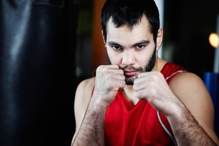 Photo for Portrait of aggressive fighter in boxing pose in gym - Royalty Free Image