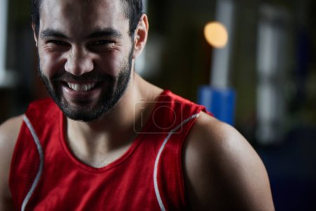 Handsome boxer in sportswear smiling and looking at camera