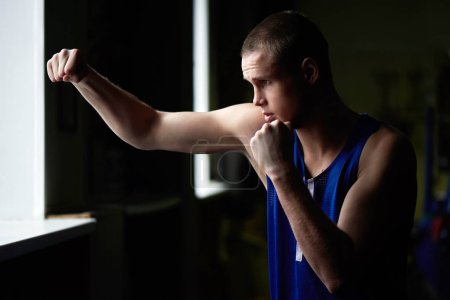 Photo for Strong boxer in sportswear training in gym - Royalty Free Image