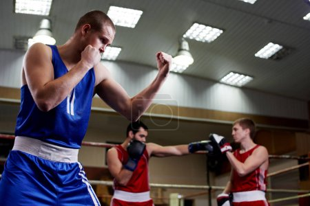 Portrait of strong boxer in sportswear in gym with sportsmen training on background