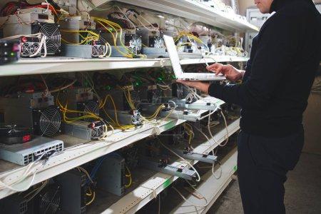 Photo pour Homme d'affaires permanent avec ordinateur portable près de ferme avec matériel pour exploitation minière cryptocurrency - image libre de droit