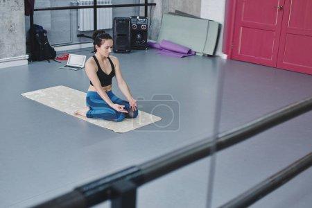 woman practicing hero yoga pose in gym, Virasana pose