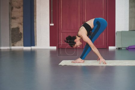 Photo for Woman practicing balance yoga pose in gym - Royalty Free Image