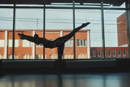 silhouette of woman practicing warrior three yoga pose in gym, virabhadrasana three pose