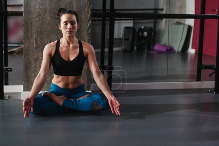 woman in padmasana pose practicing yoga with mudra in gym