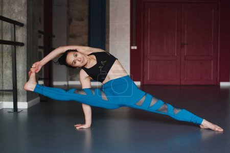 woman practicing yoga pose in gym, Visvamitrasana pose