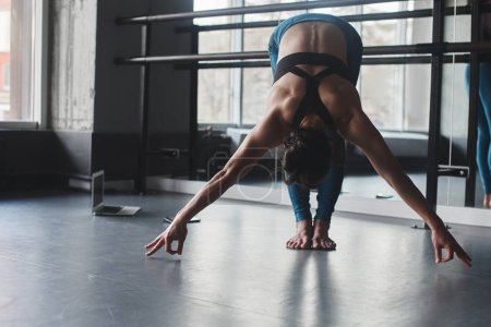 brunette woman stretching in gym, yoga concept