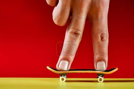 Photo pour Des doigts masculins debout sur la touche sur fond rouge, gros plan - image libre de droit