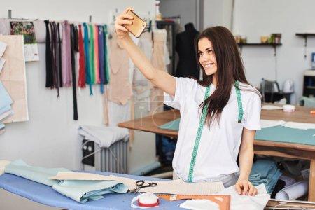 Photo pour Jolie couturière brune souriante prenant selfie sur smartphone en atelier - image libre de droit