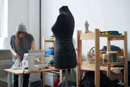Photo for Concentrated tailor putting textile on table while working on creation of clothes in atelier - Royalty Free Image