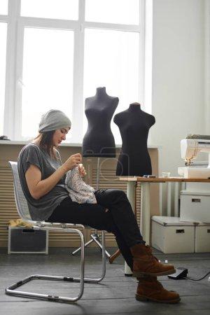 Foto de Modista confección tela sentado en silla en atelier - Imagen libre de derechos