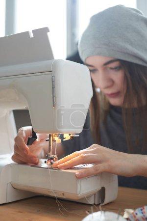 Photo pour Concentré de couturière en tissu à coudre chapeau sur machine à coudre - image libre de droit