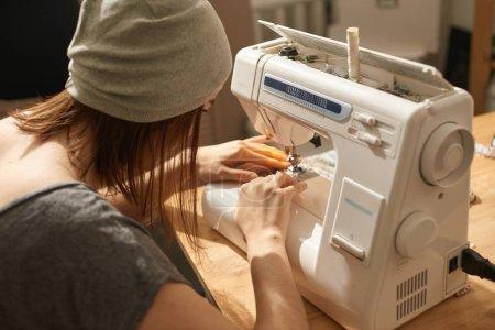 Photo pour Tissu à coudre sur mesure avec la machine à coudre dans l'atelier - image libre de droit