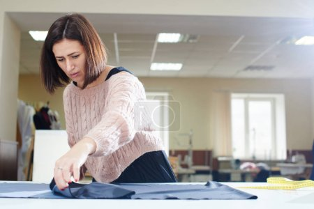 Photo for Concentrated seamstress putting textile on table and measuring with tape, creation of clothes in atelier concept - Royalty Free Image