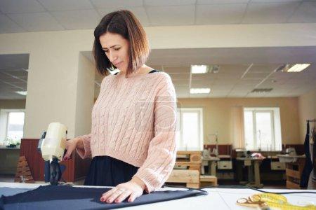 Photo pour Textile de coupe sur mesure avec un outil professionnel sur table - image libre de droit