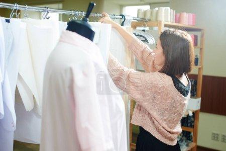Photo pour Tailleur enlevant le tissu du cintre dans l'atelier - image libre de droit