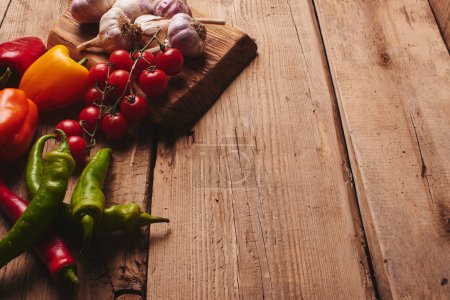Photo for Fresh organic vegetables on wooden board close up. Cherry tomatoes, garlic, peppers and dill on a wooden table - Royalty Free Image