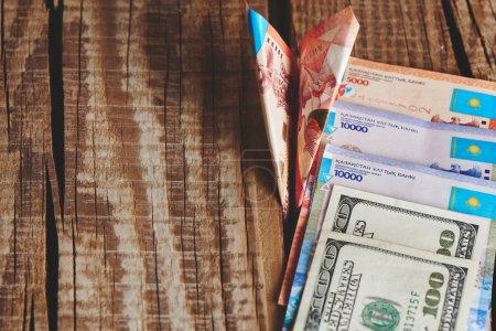 Photo pour Tas de dollars américains et tenge kazakh avec billet avion de papier sur fond en bois, gros plan concept Business and Finance - image libre de droit