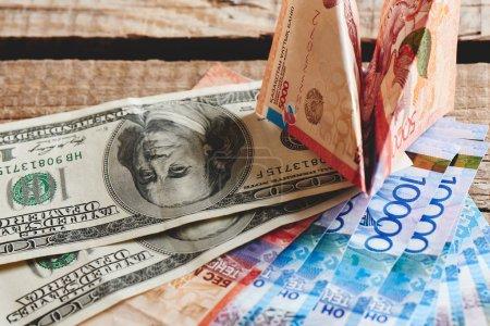 Photo pour Tas de dollars américains et tenge kazakh sur fond en bois, gros plan concept Business and Finance - image libre de droit
