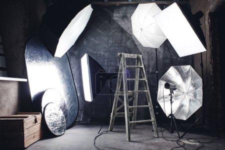 Foto-Hobby. hausgemachtes Studio im Loft-Stil mit professioneller Beleuchtung, schwarzem Hintergrund und Leiter.