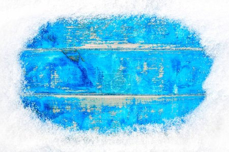 Photo for Snow frame on blue wooden background - Royalty Free Image